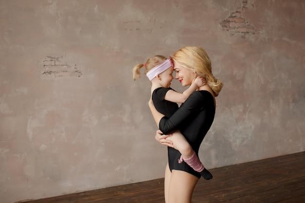 Familia feliz, dos bailarinas, madre e hija en leotardos de gimnasia negros contra la pared rosa