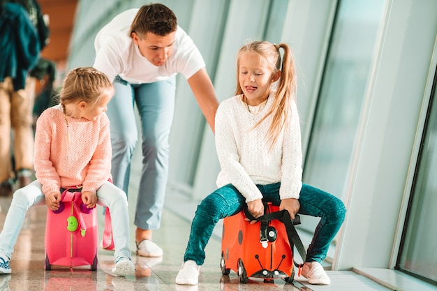 La familia feliz con dos niños en el aeropuerto se divierte esperando el embarque