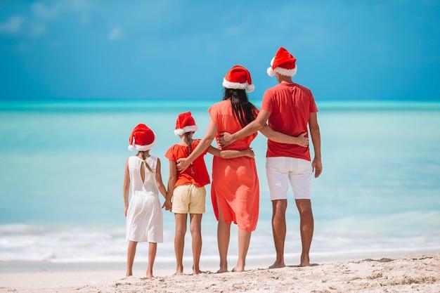 Familia feliz con dos niños en santa hat en vacaciones de verano