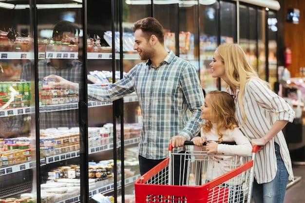Familia feliz eligiendo comestibles juntos