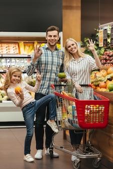 Familia feliz eligiendo comestibles y mostrando gesto bien