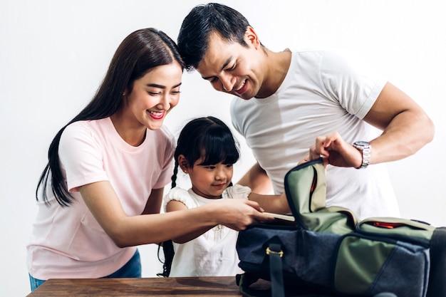Familia feliz embalaje mochila escolar con libros antes de ir a la escuela