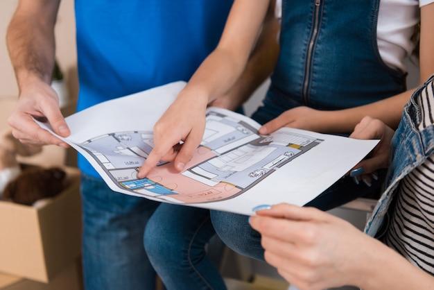 La familia feliz está estudiando el diseño de las habitaciones en el plano de la casa.