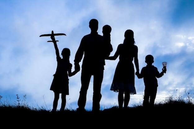 Familia feliz en el fondo de la silueta de la naturaleza