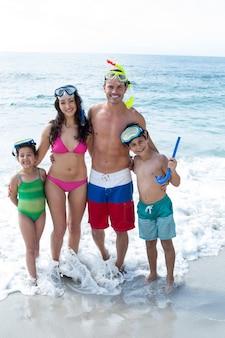 Familia feliz con gafas de buceo en la playa