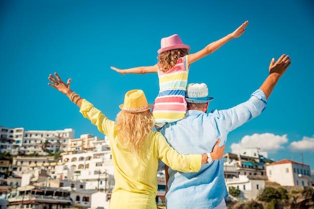 Familia feliz con gafas de sol de colores y sombreros con una ciudad europea en la vista posterior de fondo