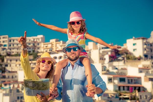 Familia feliz con gafas de sol de colores y sombreros sosteniendo un mapa con una ciudad europea en el fondo