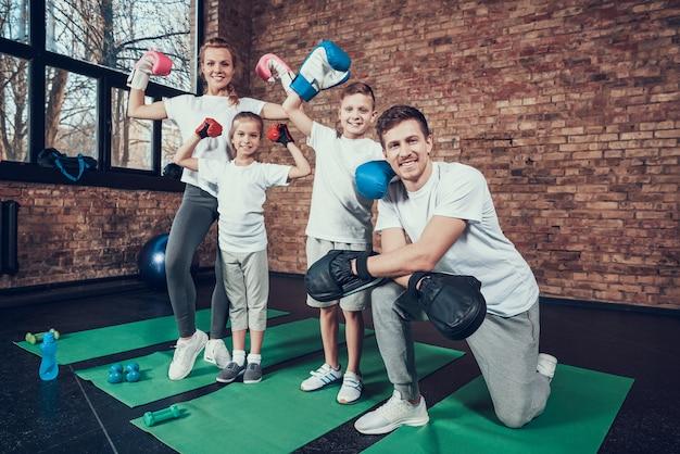 Familia feliz de ganadores de pie en el gimnasio.