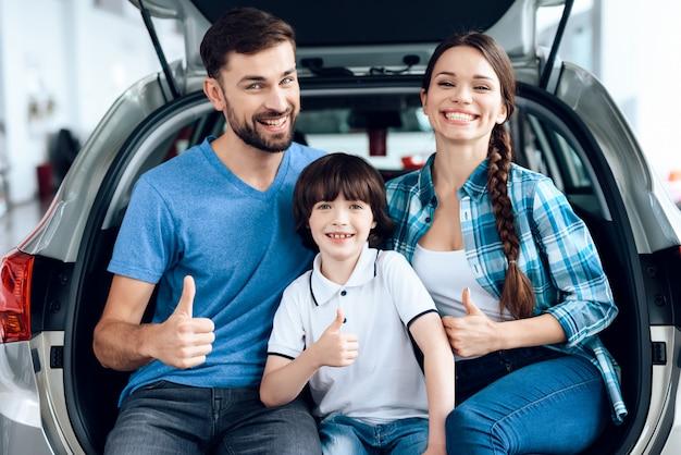 La familia está feliz de haber comprado un auto nuevo.