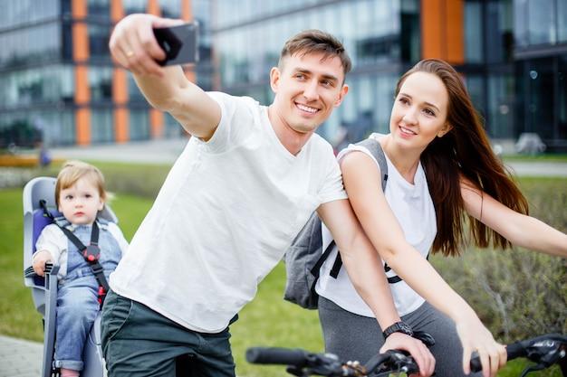 Una familia feliz hace selfie en un teléfono inteligente mientras camina en bicicleta