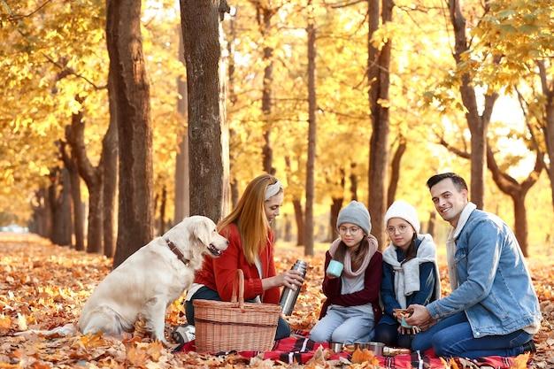 Familia feliz haciendo un picnic en el parque otoño
