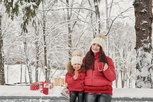 La familia feliz y la hija del niño en invierno caminan al aire libre bebiendo té. feliz madre de familia y bebé niño pequeño jugando en invierno vacaciones de navidad. familia de navidad en el parque de invierno.