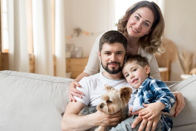 Familia feliz en el interior con lindo perro