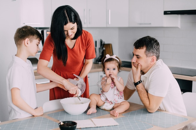 Familia feliz joven cocinando la cena juntos en la cocina