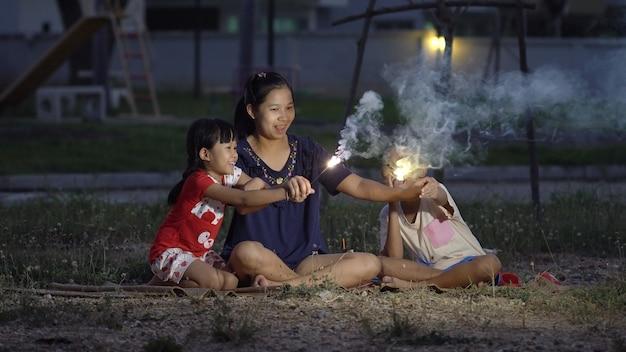 Familia feliz, joven madre con niño y niña fuego sosteniendo bengala en la noche