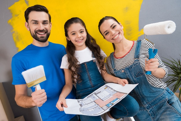 Familia feliz joven que hace reparaciones en la casa para la venta
