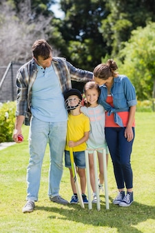 Familia feliz jugando al cricket juntos en el patio trasero