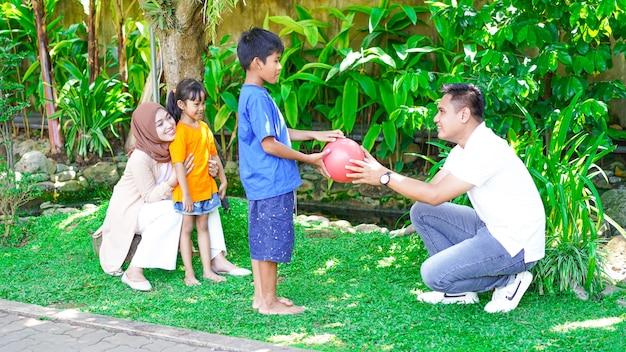Familia feliz jugando juntos en el jardín