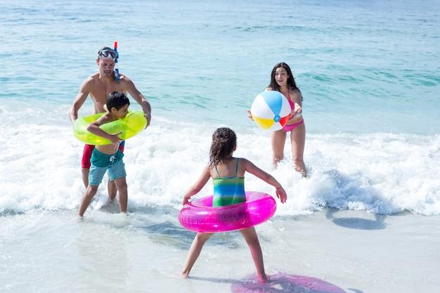 Familia feliz jugando con pelota de playa en la playa