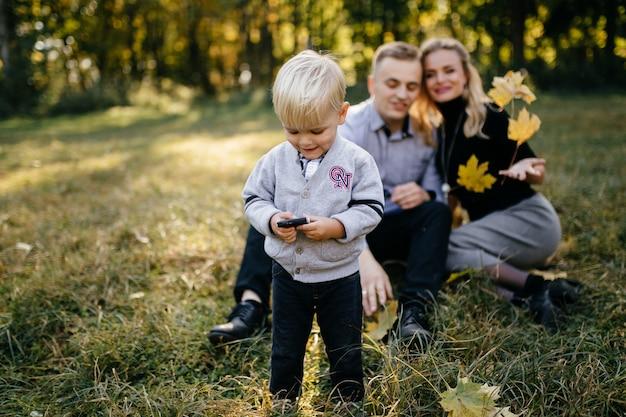 Familia feliz jugando y riendo en el parque otoño