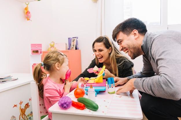 Familia feliz con juguetes en la mesa