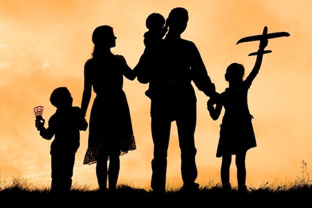 Familia feliz junto al mar en la silueta de la naturaleza