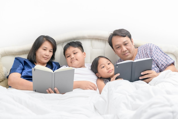 Familia feliz leyendo un cuento en la cama