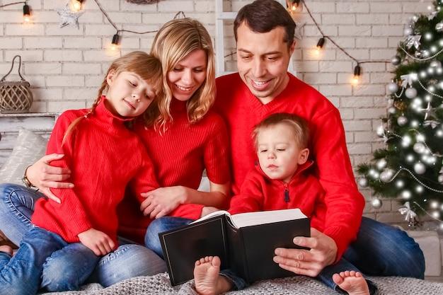 Familia feliz leyendo un libro en casa en navidad