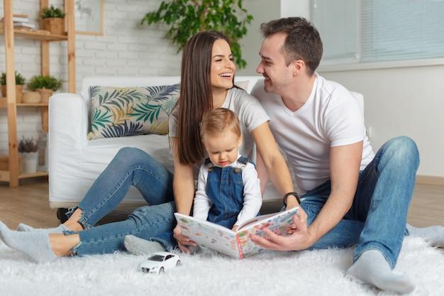 Familia feliz leyendo un libro juntos