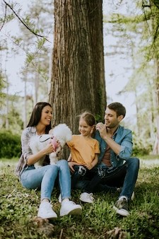 Familia feliz con lindo perro bichón en el parque