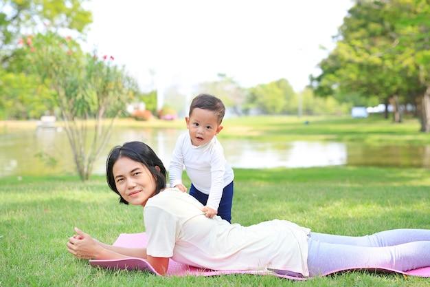 Familia feliz madre asiática y su hijo acostado en el césped verde