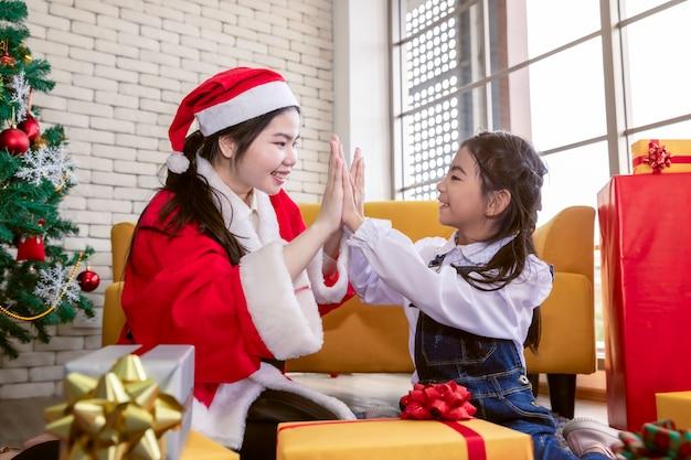 Familia feliz madre e hija hija haciendo y dando regalos en navidad.