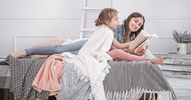 Familia feliz. madre e hija leyendo un libro en la cama.