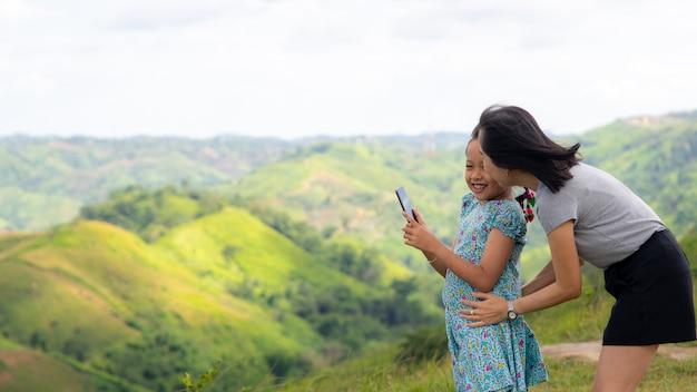 Familia feliz de madre e hija tomando selfie en la cima de la montaña