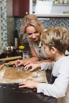 Familia feliz. madre e hijo hijo hornear galletas de jengibre para navidad