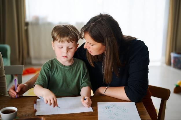Familia feliz. madre con hijo pequeño pintando y dibujando juntos. niño caucásico con su madre estudiando en casa