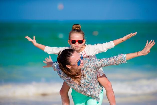 Familia feliz de madre y niña en playa blanca