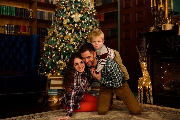 Familia feliz madre padre y bebé en el árbol de navidad en casa