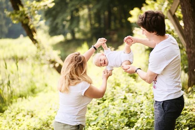 Familia feliz. mamá y papá se divierten con su pequeño hijo descansando en un parque verde de verano