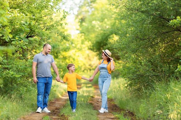 Familia feliz, mamá, papá, hijo a pie, tomados de la mano al aire libre en verano.