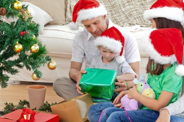 Familia feliz mirando al niño abriendo un regalo de navidad