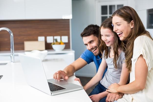 Familia feliz mirando portátil