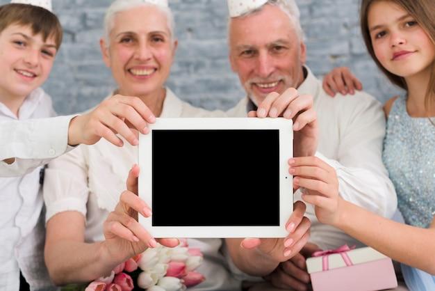 Familia feliz mostrando tableta digital de pantalla en blanco