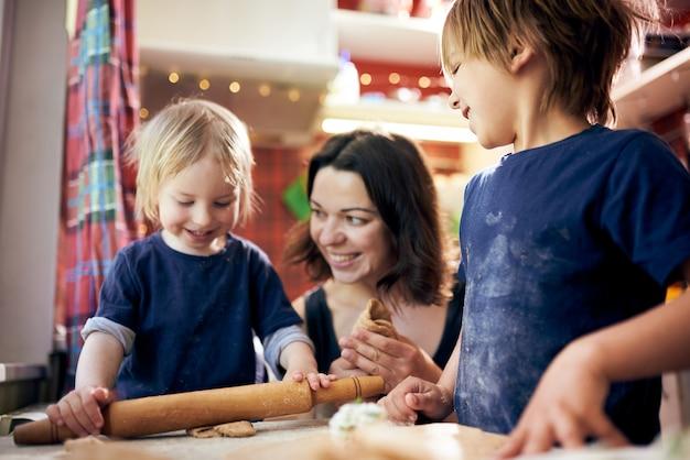 Familia feliz muchachos divertidos y su madre están preparando la masa