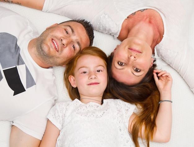 Familia feliz con el niño en la cama sonriendo