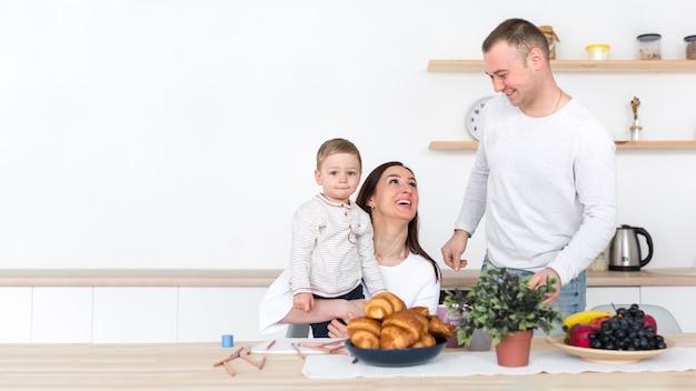 Familia feliz con niño en la cocina y espacio de copia