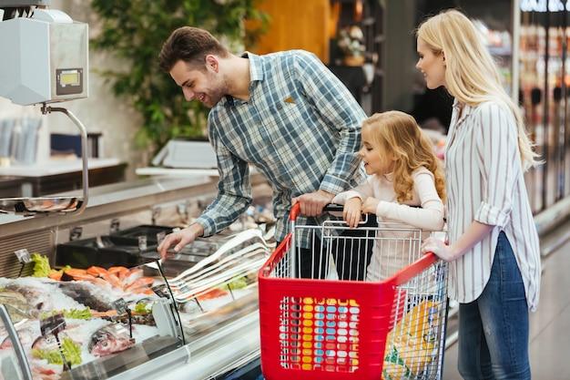 Familia feliz con niño comprando comida
