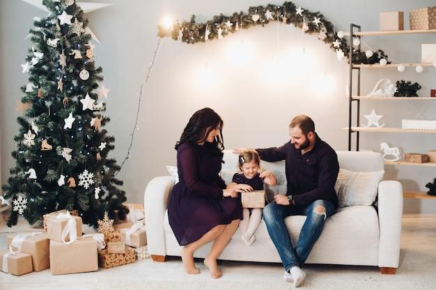 Familia feliz con un niño se sienta en el sofá junto al árbol de navidad y se relaja