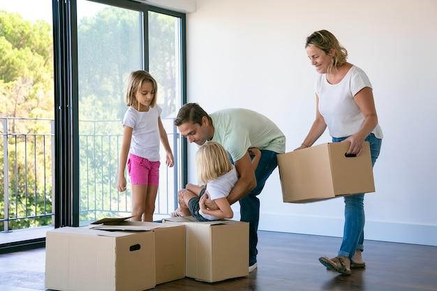 Familia feliz con niños cerca de cajas de cartón de pie en la sala de estar