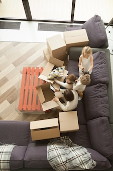 Familia feliz y niños desempacando cajas moviéndose hacia adentro, vista superior